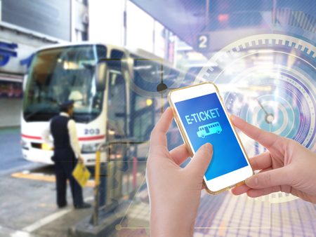 online service: Hand holding mobile phone with E-Ticket word with blur bus terminal  background,Digital Marketing concept; retro color effected