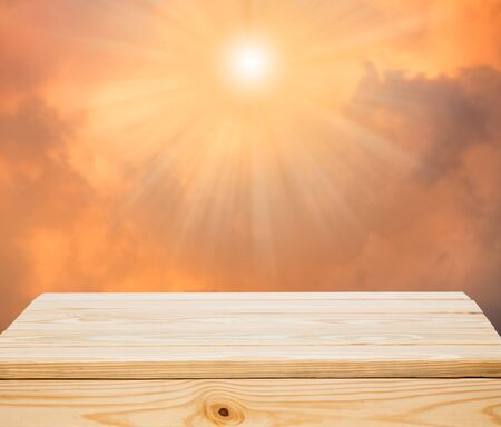 sunlight sky: Wood table top with orange clouds and sunlight background