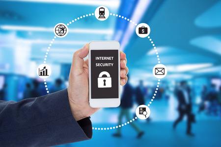 Hand holding mobile phone with Internet security on screen