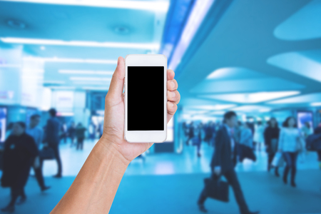 Hand holding mobile phone with blurred image of business people background