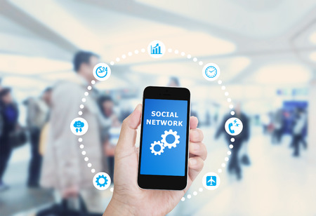 Hand holding Smartphone with Social network graphic icon design on blurred image of business people background Stock Photo
