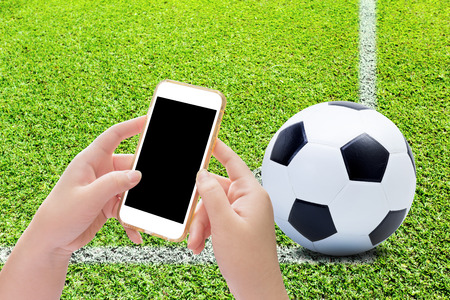 conner: Hand holding smartphone with soccer ball on play fields