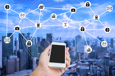 wireless network: Hand holding smartphone with smart city and internet of things concept Stock Photo