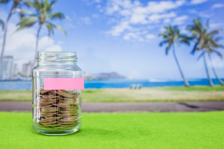 Coins in glass bottle with blur Hawaii island background Stock Photo