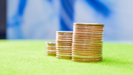 Stack of coins on green background Stock Photo