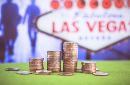 gambler: Stack of US. dallor coins with Las vegas sign background Stock Photo