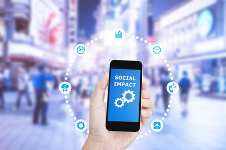 Hand holding mobile phone with Social impact on screen on Blurred image of street market Stock Photo