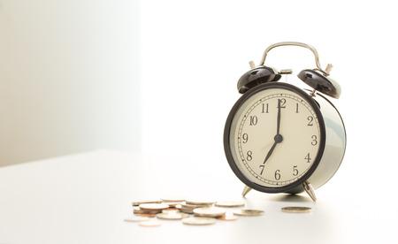 Vintage clock at seven oclock and coins