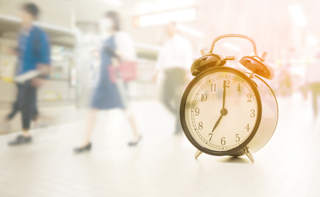 seven o'clock: Double exposure of Vintage clock at seven oclock and blurred image of people traveling Stock Photo