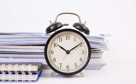 Vintage clock and stack of paper on white background
