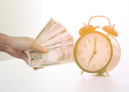buying time: Double exposure of Businessman hand holding Japanese banknote and vintage clock at 7 oclock Stock Photo