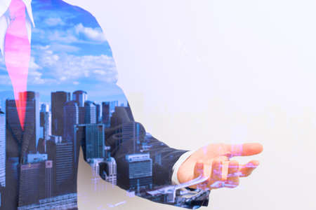 Double exposure of businessman hand open with cityscape