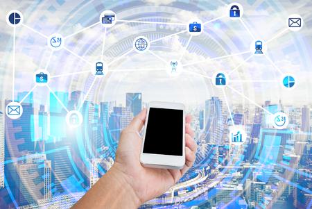 Main tenant le téléphone portable avec double exposition de fond de conception graphique de paysage urbain et business technologie. Technique mixte