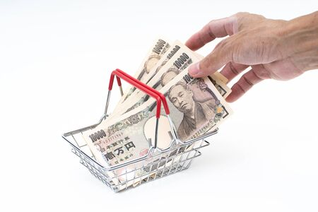 Man hand grabbing Japanese 10000 banknote in shopping basket on white background 版權商用圖片