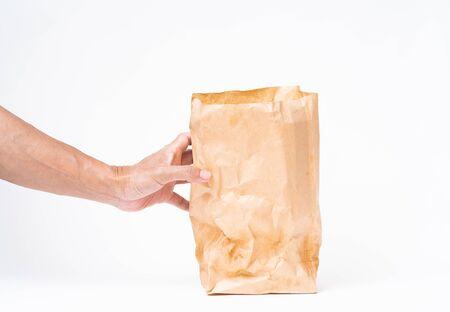 Mannhand, die braune Papiertüte auf weißem Hintergrund hält