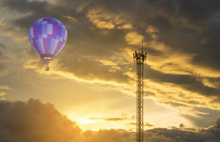 Violet hot air balloon with telecom pole and dramatic sky at sunset