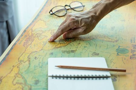 Hand pointing on America map with blank notebook