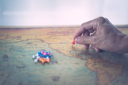Man hand pin pointing on United States of America map