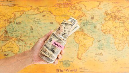 Man hand holding bottle of saving travel money with world map background Stock Photo