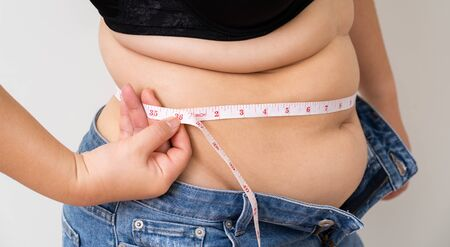 Overweight women with tape measuring her belly