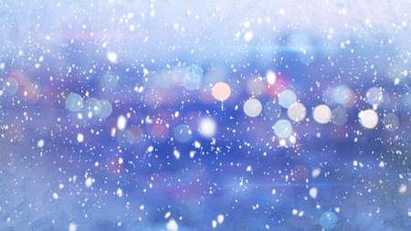 christmas winter: snowfall and defocused lights evening wintry city