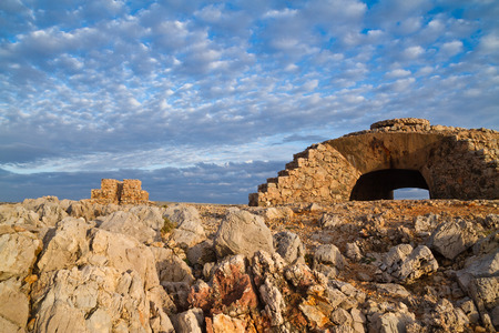 Machine gun and mortar nests and batteries, built during spanish civil war in the Nati point. In the background appears the famous lighthouse. One of the most touristic places of Menorca, Spain.