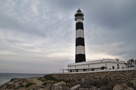 Lighthouse of Artrutx piont, one of the most famous and picturesque buildings of Menorca, Spain Stock Photo
