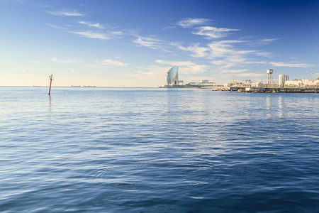 BARCELONA, SPAIN - December 11, 2016: Barceloneta Beach, Montjuic, Port Olimpic and Hotel Vela, located on front line beach of Barcelona. Around Barceloneta neighborhood. Looking from the sea.