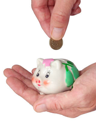 deposits coin in piggy bank on white of bakgraund