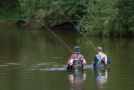 redes de pesca: Dos pescadores est�n en el r�o y los peces  Foto de archivo