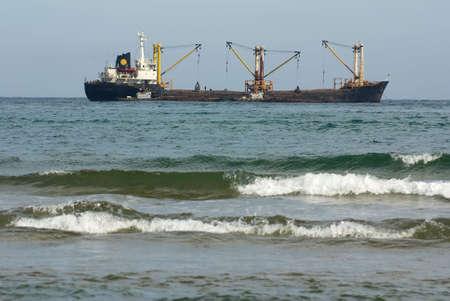 sea nave near by coast gets cargo Stock Photo