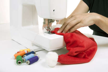 woman sewing a hat for Santa Claus on the sewing machine photo