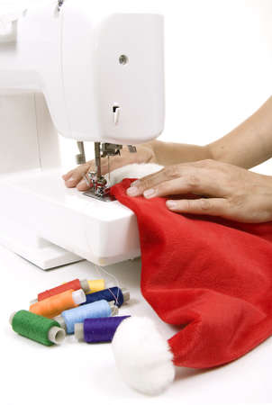 woman sewing a hat for Santa Claus on the sewing machine Stock Photo