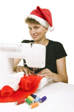 woman sewing a fur coat for Santa Claus on the sewing machine photo