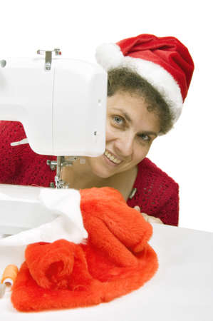 woman sewing a fur coat for Santa Claus on the sewing machine Stock Photo