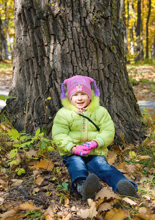 girl sits under tree in autumn park Stock Photo - 12613832