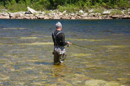 fisherman fishing on a mountain river in Siberia photo