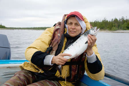 salmon fishing: fisherman holds salmon fishing in the sea