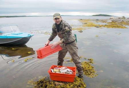 fisherman on the shore of the Barents Sea fish Stock Photo