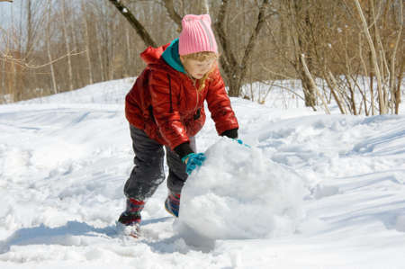 girl rolls a snowball in the forest Stock Photo