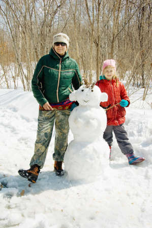 Mother and daughter next to a snowman in a forest