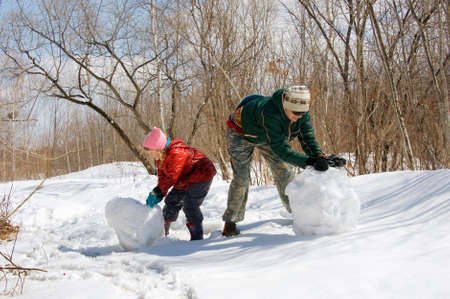 Mother and daughter ride a snowball in the forest