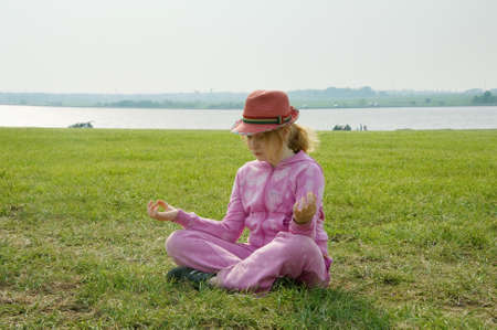 girl in the hat meditating on the beach Stock Photo