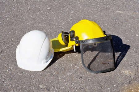yellow and white construction helmets on the pavement