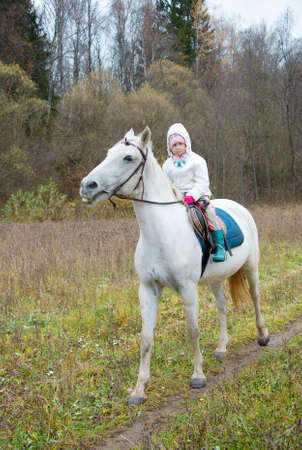 Girl riding on a white horse in a field photo