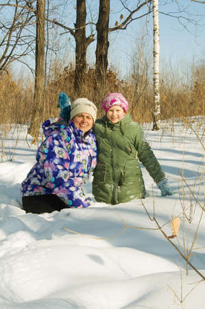 woman with a little girl playing in the winter forest photo