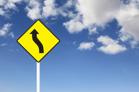 Winding road sign under the blue sky
