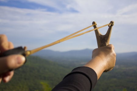 Mano sling tira tiro se prepara para el lanzamiento de semillas de árboles en el bosque