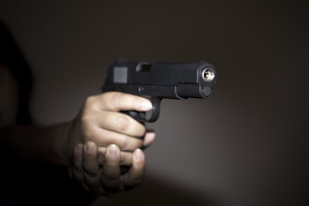 Hand holding gun preparing to fire photo