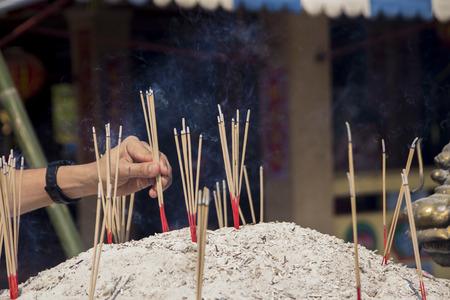 incense sticks: Hand placing incense sticks in the pot